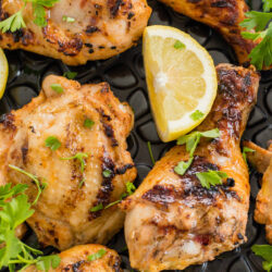 Grilled chicken legs and thighs garnished with lemon wedges and parsley.