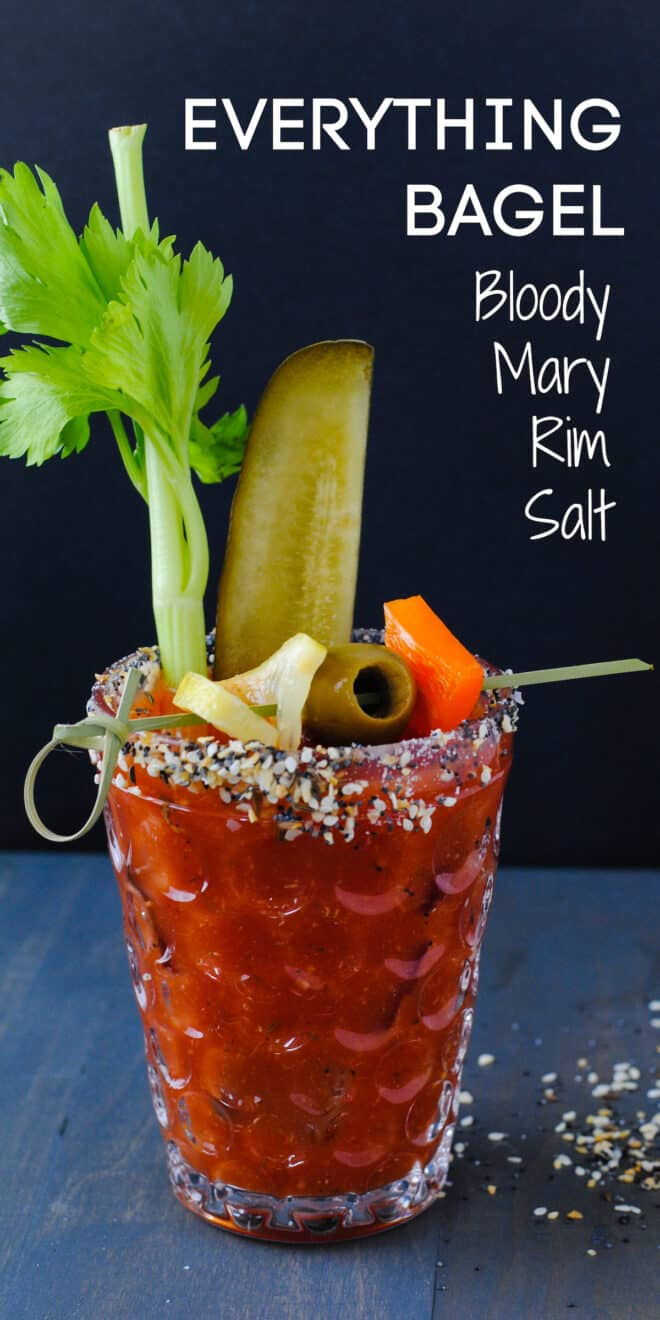 Bloody Mary in a textured glass, garnished with pickles, celery and an olive skewer, with overlay: EVERYTHING BAGEL Bloody Mary Rim Salt.