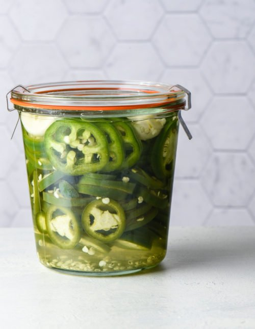 Jar of pickled jalapenos against light background.