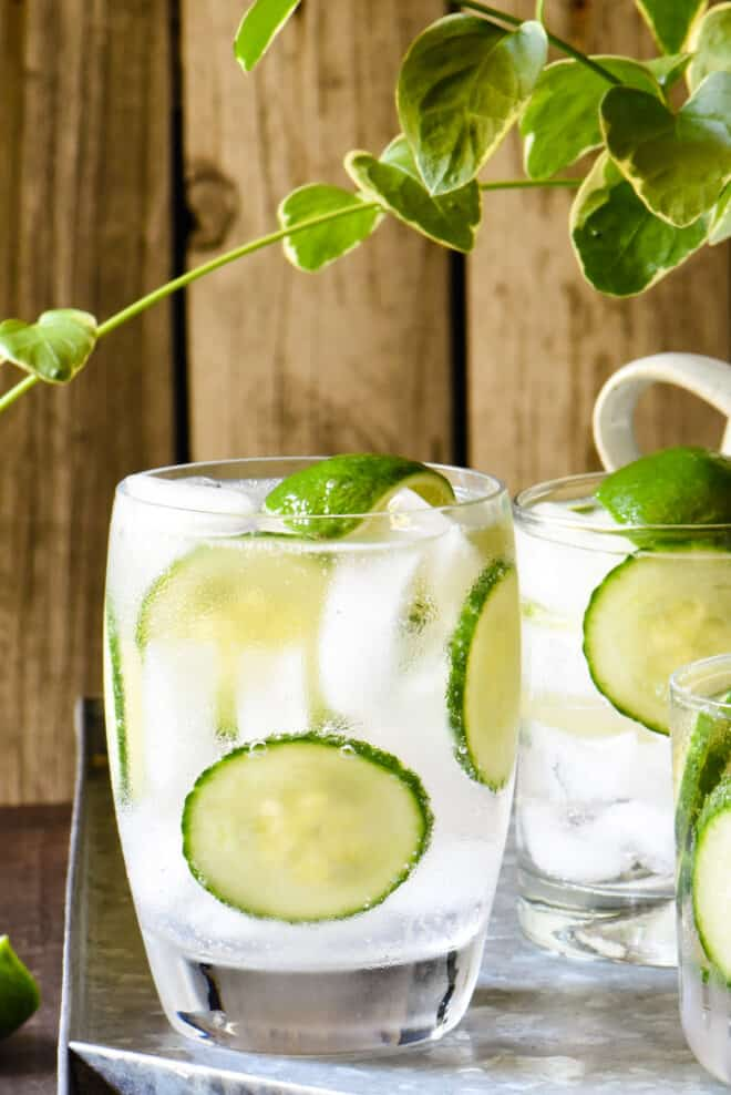 Close up on a White Claw cocktail over ice in a small glass, garnished with limes and cucumber slices.