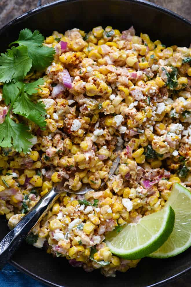 Mexican roasted corn salad in a black bowl, garnished with lime wedges.
