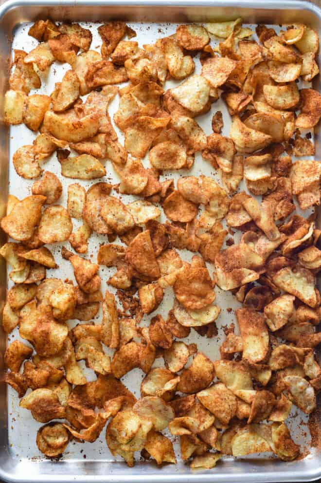 Stainless steel sheet pan of hot potato chips covered in spices.