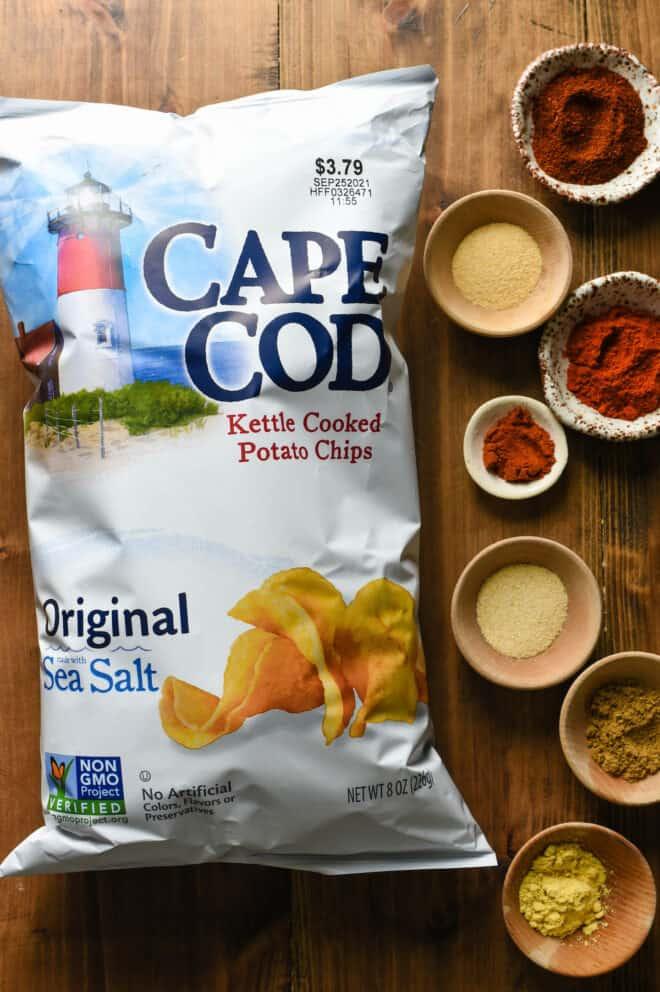 Bag of kettle crisps alongside small ramekins of various ground spices.